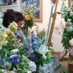 Tisha Wood painting a bouquet in acrylic in Lillian Kennedy's studio